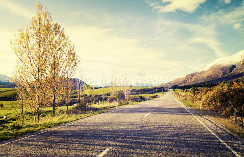 Autumn Themed Country Road With-Gebirgszug-Konzept stockbilder
