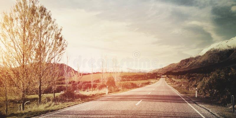 Autumn Themed Country Road With-Gebirgszug-Konzept stockfoto