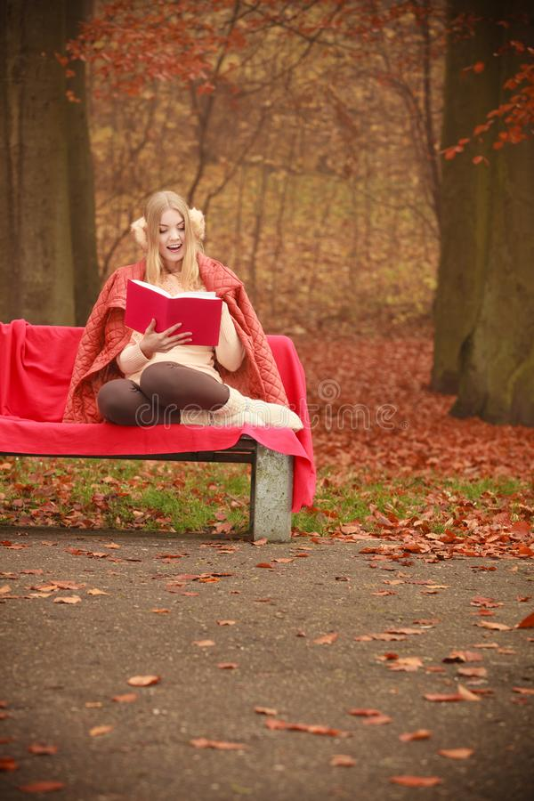 Blonde girl reading book in autumn scenery royalty free stock photo