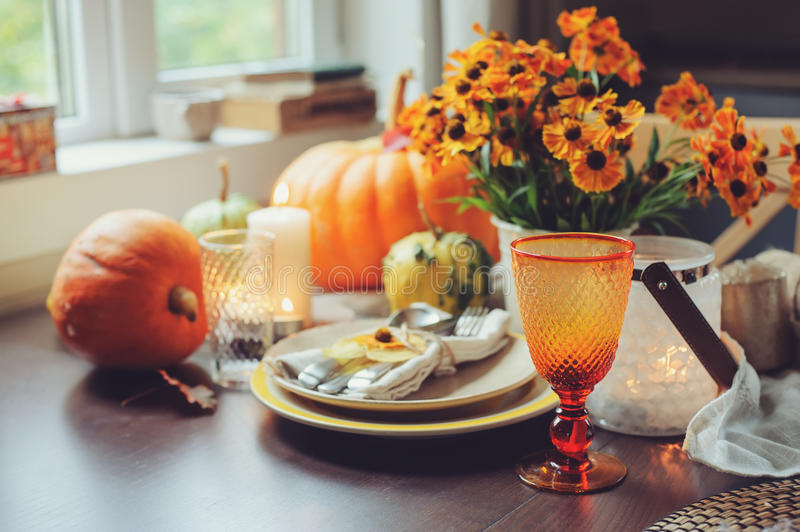 Autumn traditional seasonal table setting at home with pumpkins, candles and flowers. Celebrating Thanksgiving royalty free stock image