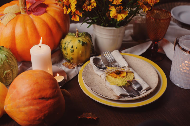 Autumn traditional seasonal table setting at home with pumpkins, candles and flowers. Family celebrating Thanksgiving day stock image