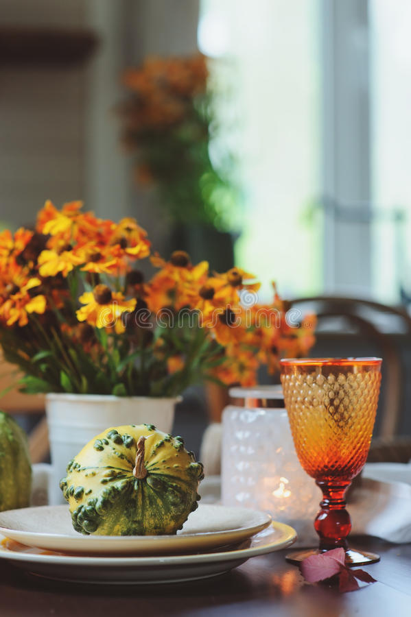 Autumn traditional table setting for Thanksgiving or Halloween, with candles, flowers and pumpkins. royalty free stock images