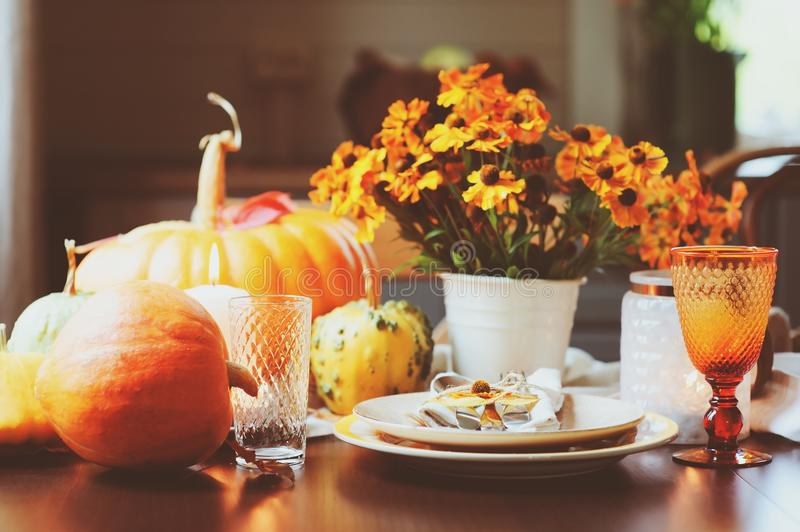 Autumn traditional table setting for Thanksgiving or Halloween. With candles squash and pumpkins stock photos