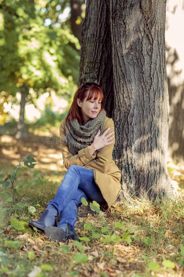 Autumn trees, fall season. Fun in the autumn forest. Smiling ginger woman enjoying in nature stock photo