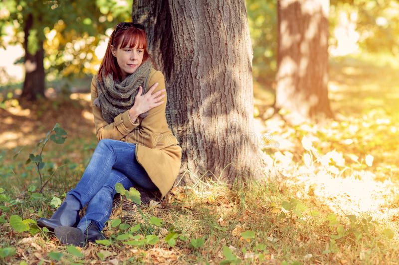 Autumn trees, fall season. Fun in the autumn forest. Smiling ginger woman enjoying in nature stock photography