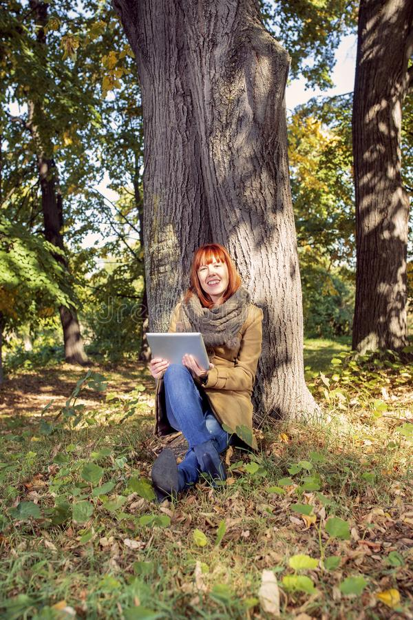 Autumn trees, fall season. Fun in the autumn forest. Smiling Woman with digital tablet in autumn park stock photo