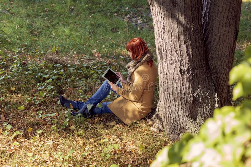 Autumn trees, fall season. Fun in the autumn forest - woman using tablet outdoor royalty free stock image