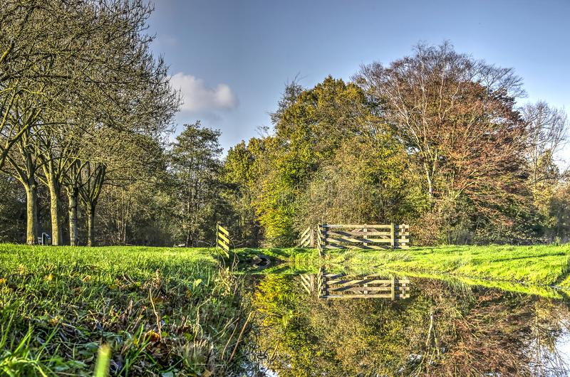 Autumn trees, fence and canal. Wooden fence, autumn trees and grass fields reflecting in a canal in a public park in Woerden, The Netherlands stock photography