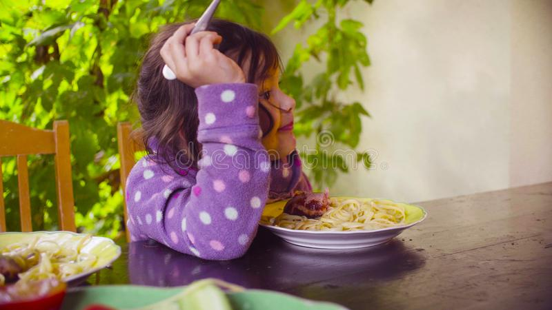 Two naughty girls are sitting at the table and eating pasta and fried sausage. Autumn. Two naughty girls are sitting at the table and eating pasta and fried stock image