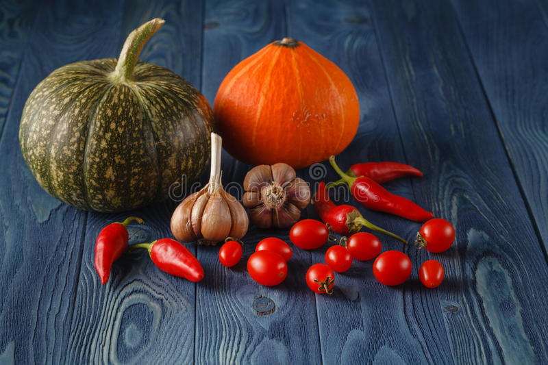 Autumn vegetables cooking preparation. Pumpkin, tomatoes ingredients on blue rustic background royalty free stock photos