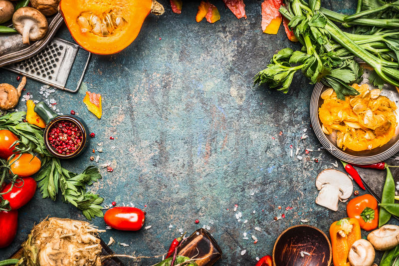 Autumn vegetables cooking preparation . Pumpkin, tomatoes, root vegetables and mushrooms ingredients on dark rustic background for stock photos