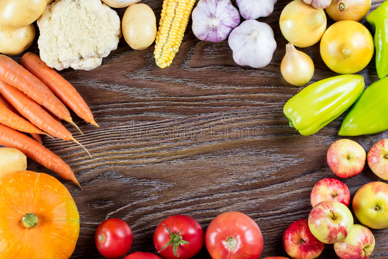 Autumn vegetables harvest, frame, raw healthy organic food on wooden background royalty free stock image
