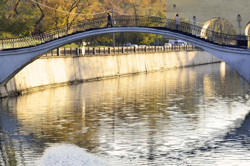 Autumn. View of the bridge over the river in the city on which the man and the woman parted. Autumn. View of the bridge over the river in the city on which the stock photo