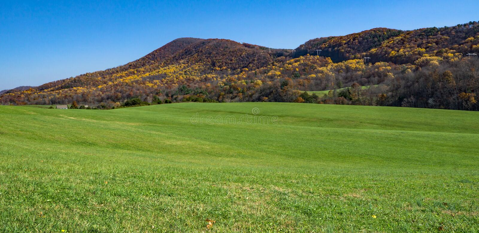 Autumn View of Catawba Mountain. With a green meadow in the foreground located in Jefferson National Forest, Roanoke County, Virginia, USA royalty free stock photo