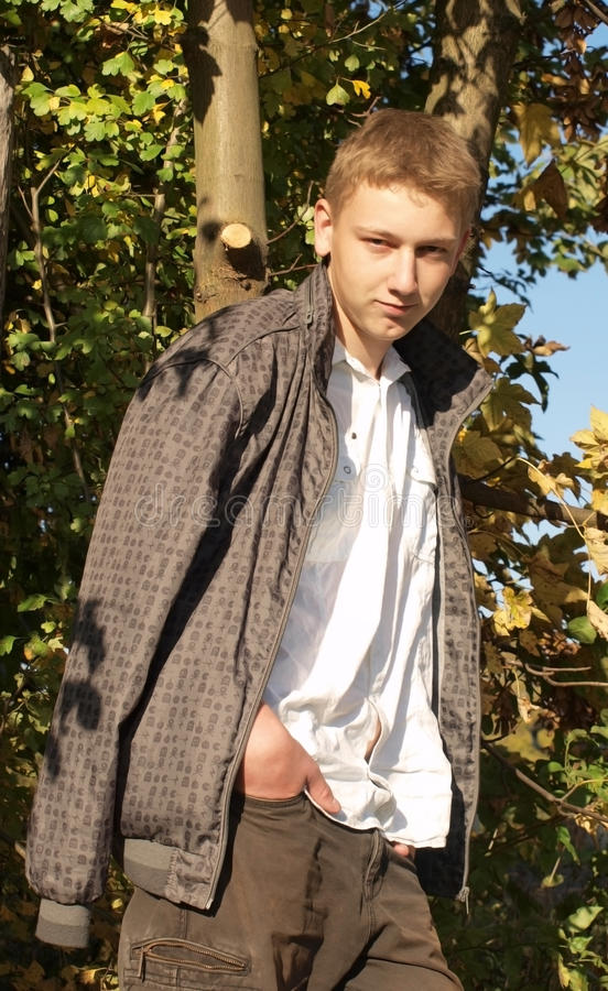 Autumn walk. Autumn (fall) portrait of young man (teen) (blond, blue eyed) in the autumn landscape wearing white shirt and grey jacket royalty free stock photo
