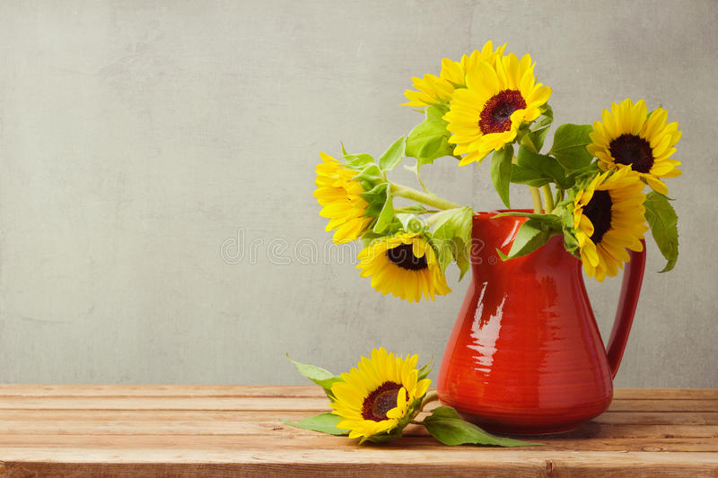Autumn wallpaper. Sunflowers in red vase on wooden table.  stock images