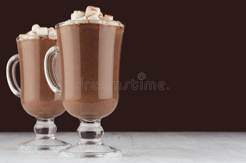 Autumn warm drink - hot cocoa with marshmallows, cocoa powder on dark brown background, copy space. Autumn warm drink - hot cocoa with marshmallows, cocoa stock images