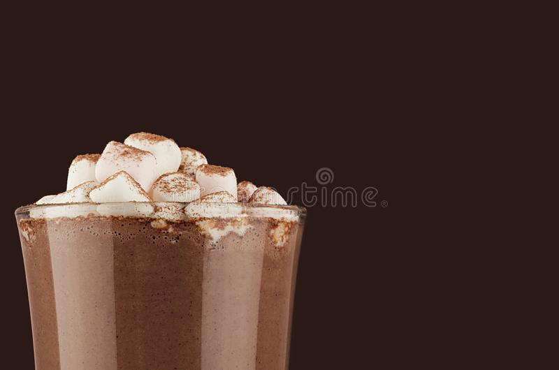 Autumn warm drink - hot cocoa with marshmallows, cocoa powder closeup, details, top section on dark brown background, copy space. Autumn warm drink - hot cocoa stock photography