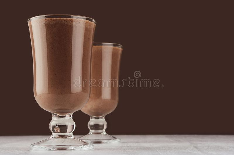 Autumn warm drink - two hot cocoa in wineglass on dark brown background, copy space. Autumn warm drink - two hot cocoa in wineglass on dark brown background stock images
