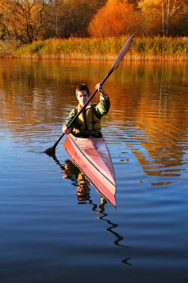 Autumn water. Teen kayaking on the river in autumn stock photos