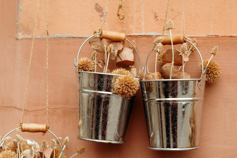 Wedding decor buckets with dried flowers on the background of a shabby wall. Autumn wedding decor buckets with dried flowers on the background of a shabby wall royalty free stock images