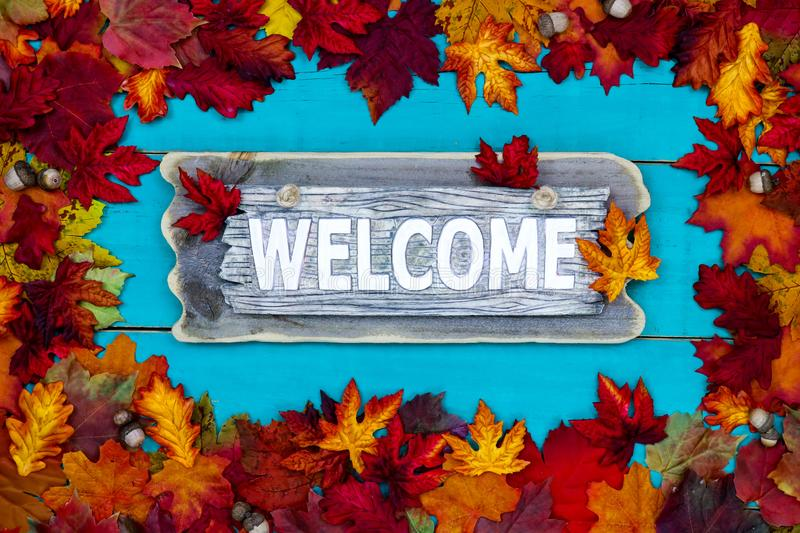 Autumn Welcome sign. Welcome sign with colorful fall leaves border hanging on antique rustic teal blue wood background; autumn, Thanksgiving, Halloween, seasonal royalty free stock photography