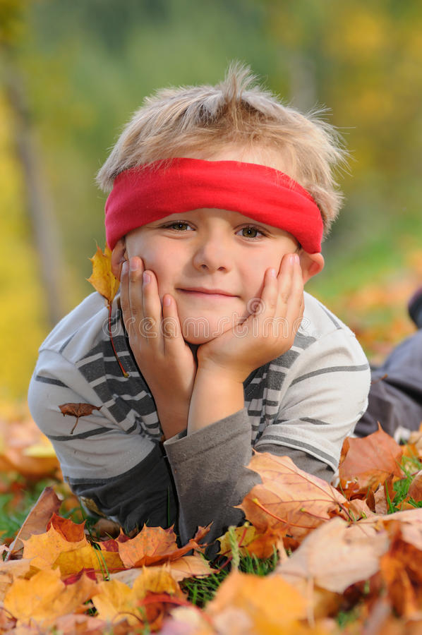Autumn well being. Young boy with red headband lying on green grass with autumn leaves, well being and looking to the camera royalty free stock photography