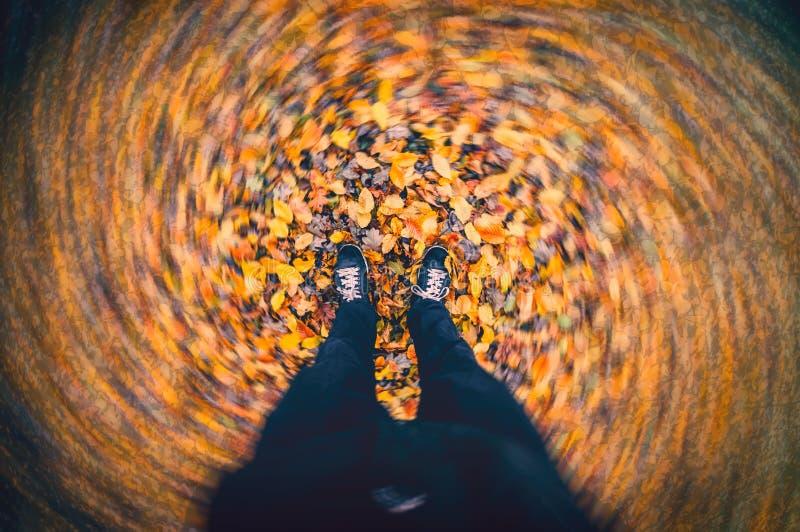 Autumn Wind Blowing Fallen Leaves che turbina intorno ai piedi dell'uomo fotografia stock libera da diritti
