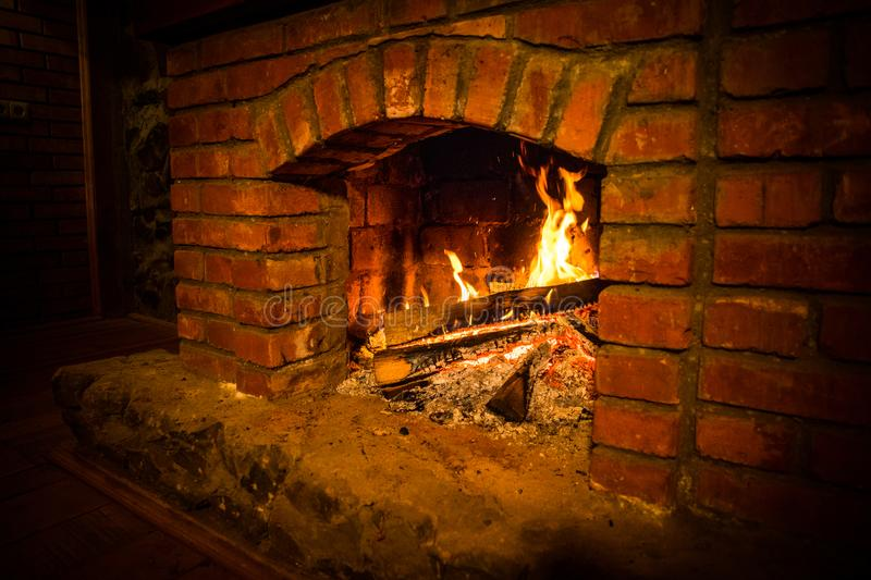 Autumn or winter burning fireplace cozy evening concept close up. Close up shot of burning firewood in the fireplace royalty free stock photo