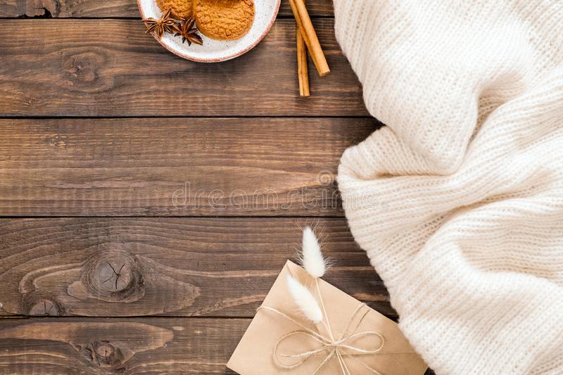 Autumn or winter flatlay composition with white wool plaid, crft paper envelope, cinnamon sticks, cookies, dry flowers. Cozy home royalty free stock images