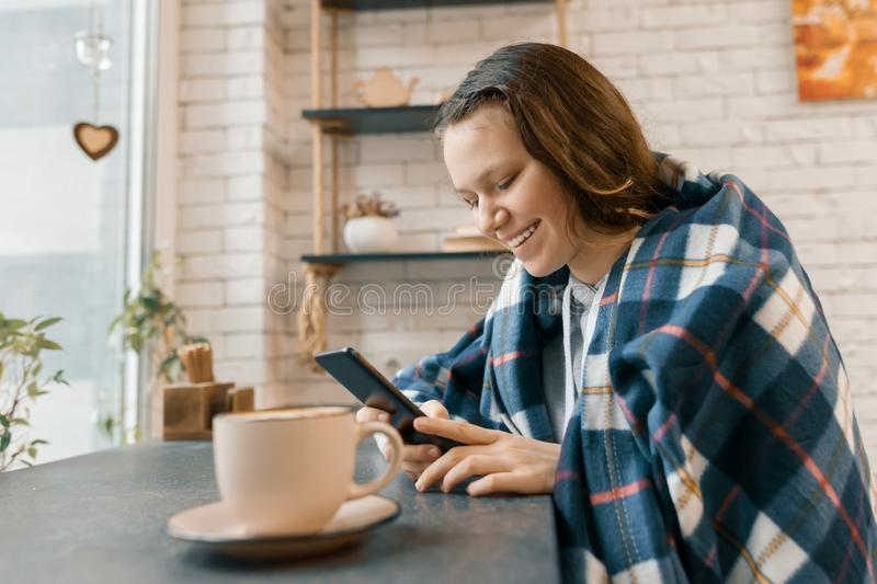 Autumn winter portrait of smiling teen girl with mobile phone and cup of coffee in coffee shop, girl covered with woolen plaid bla royalty free stock images