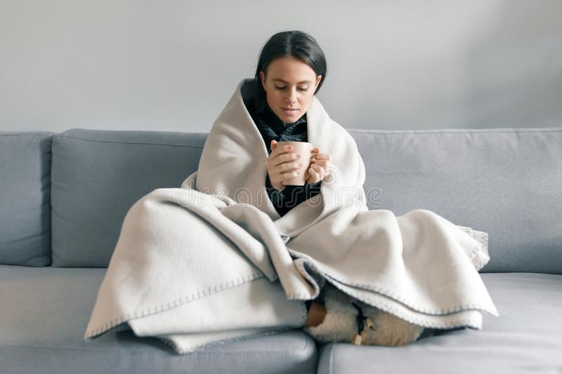 Autumn winter portrait of young girl resting at home on the sofa with cup of hot drink, under warm blanket.  royalty free stock image
