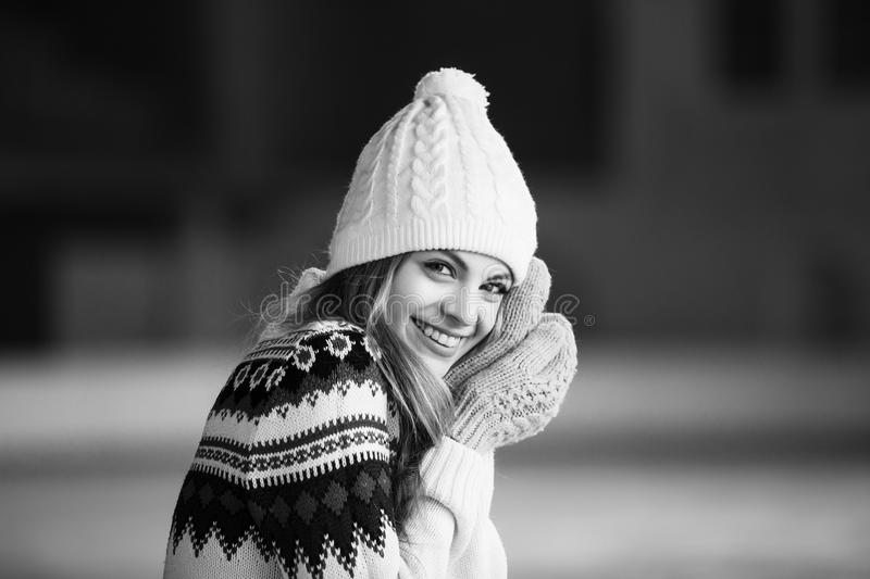 Autumn, Winter portrait: Young smiling woman dressed in a warm woolen cardigan, gloves and hat posing outside. Black and royalty free stock photo