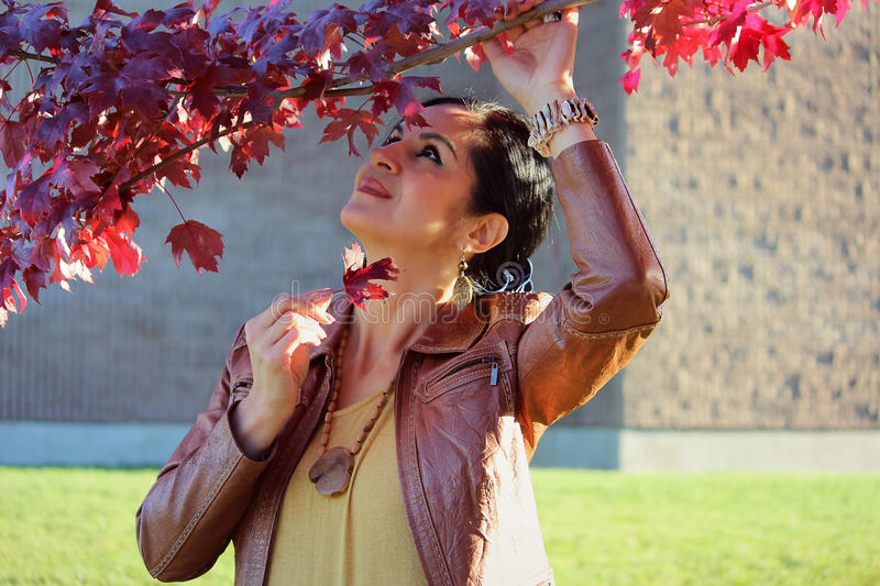 Autumn woman. Beautiful, fashion woman enjoying a beautiful autumn day, outside. Close up portrait of Caucasian woman, holding a maple branch and looking up royalty free stock photo