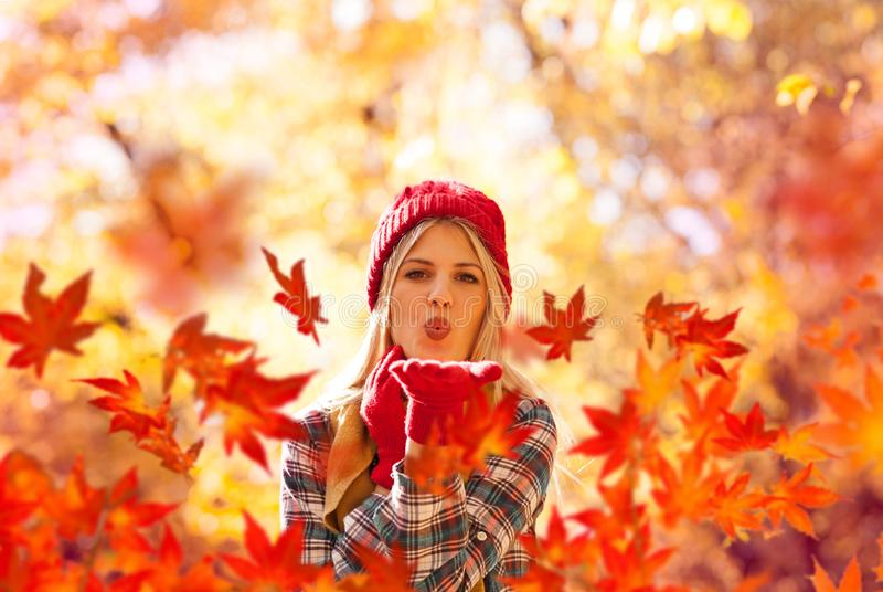 Autumn woman blowing fall leaves. Autumn season, change weather, fall is coming stock image