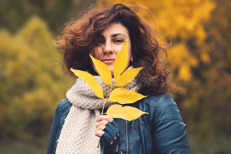 Autumn woman brunette with yellow fall leaf in park royalty free stock images