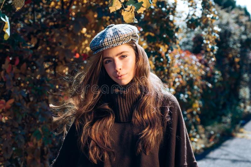 Autumn woman. Carefree young woman in trendy vintage red pullover or sweater. Beautiful happy smiling girl with long. Hair wearing stylish jacket posing in royalty free stock photo