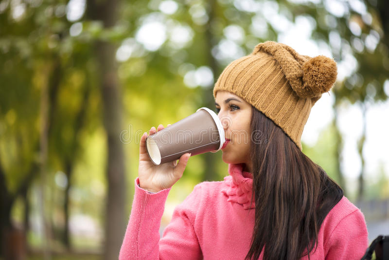 Autumn woman drinking coffee on park bench under fall foliage. royalty free stock image