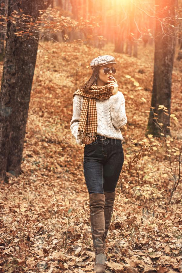 Autumn Woman enjoy smoking alone. Lonely smoker. Autumn is here. Pretty woman in hat and sunglasses smoking cigarette. Forest background. Fall fashion accessory royalty free stock photo