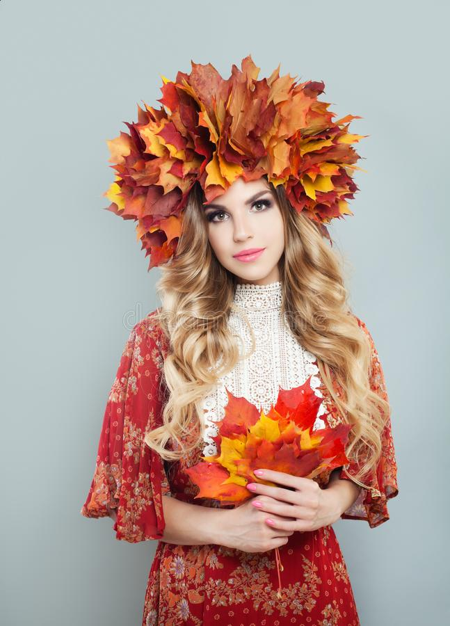 Autumn woman in fall leaves crown holding red leaves in hands on gray background. Pretty model with blonde curly hair and makeup.  royalty free stock photos