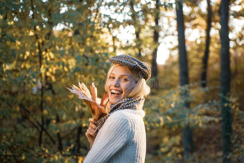 Autumn woman. Fashion autumn portrait woman with yellow maple leaves on nature background. Pretty woman walking in the stock image