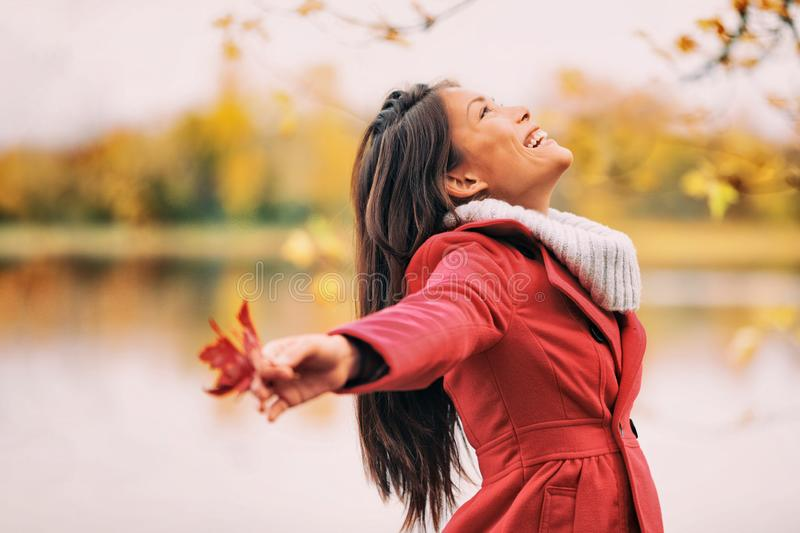 Autumn woman happy smiling feeling free in fall nature. Nature people beauty landscape. Girl by the lake stock photo