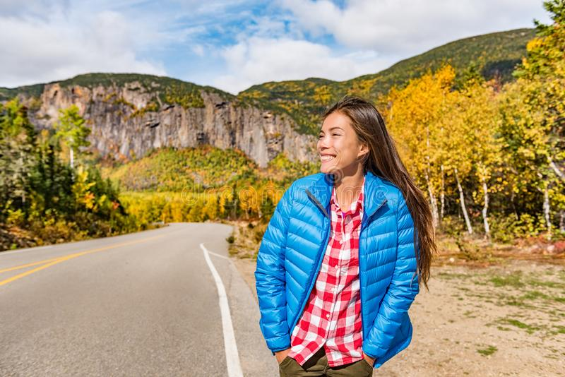 Autumn woman hiker travel lifestyle. Asian girl wearing down jacket in cold weather in canadian nature, Quebec park in fall season royalty free stock photography