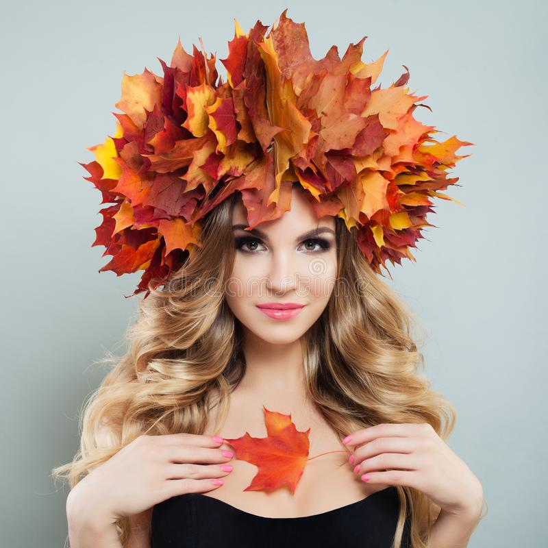 Autumn woman holding fall leaves. Nice model with makeup and curly hair.  stock image
