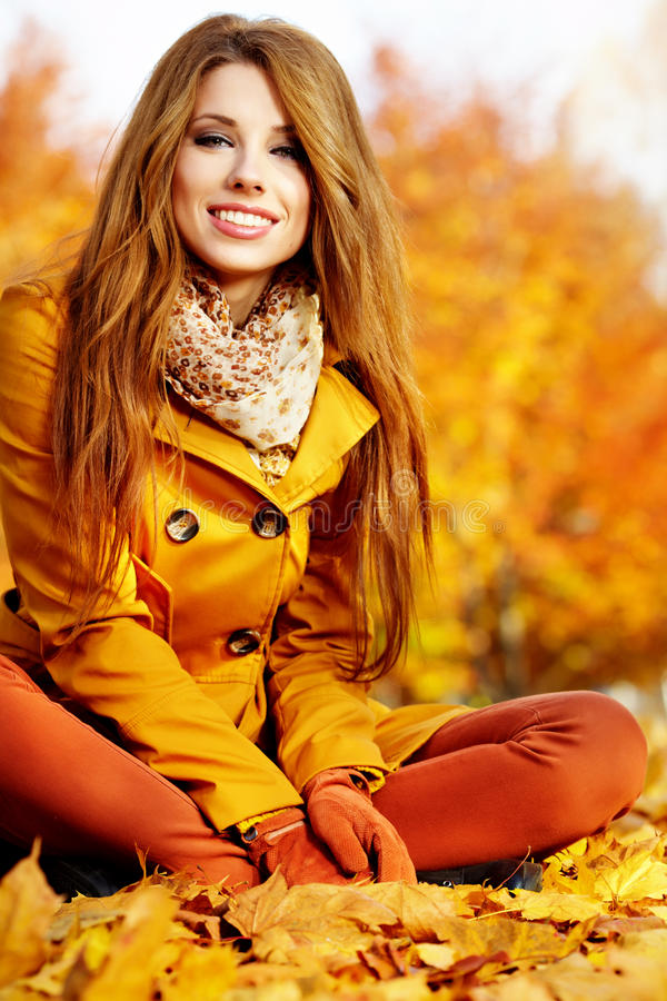 Autumn woman lying over leaves and smiling royalty free stock photo