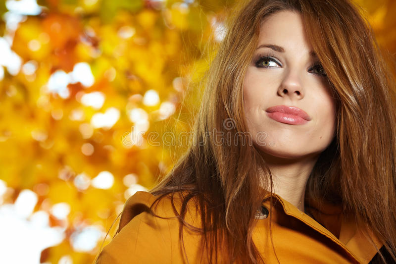 Autumn woman lying over leaves and smiling royalty free stock photography