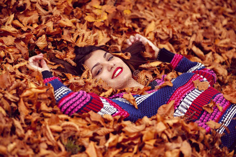 Autumn woman lying over leaves and smiling stock images