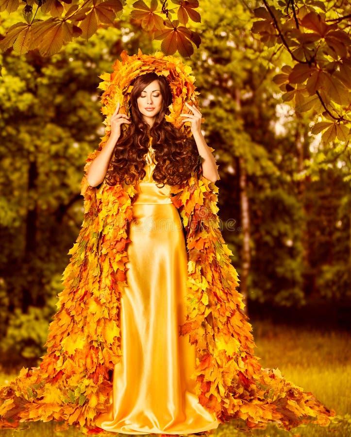 Autumn Woman modemodell i nedgångskogen, gul sidaklänning royaltyfri fotografi
