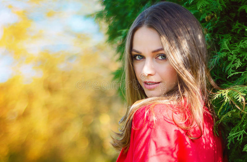 Autumn woman portrait smiling outdoors at the park. stock photo