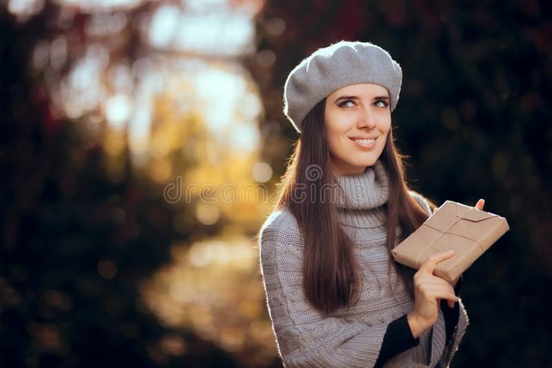 Retro Chic Girl with Beret Holding a Paper Wrapped Package. Autumn woman receiving a package by traditional mail royalty free stock photos